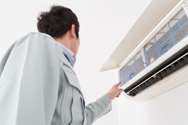 エアコンを掃除する男性