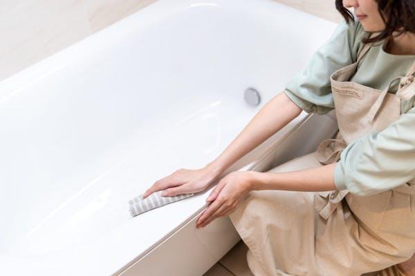 お風呂の水垢をスポンジで掃除する女性
