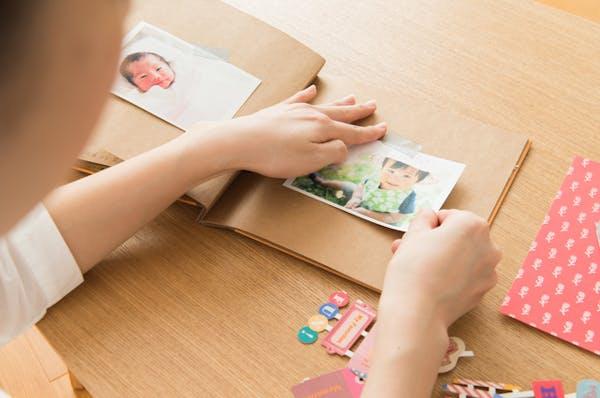 女性らしき手が赤ちゃんの写真を使用してアルバムを作ろうとしている