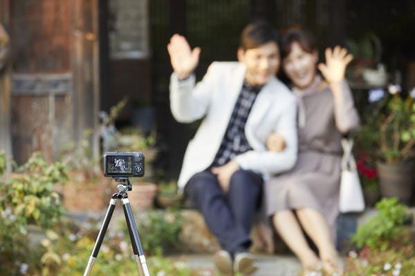 三脚で自撮りをするカップル