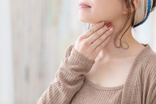 喉を抑える女性
