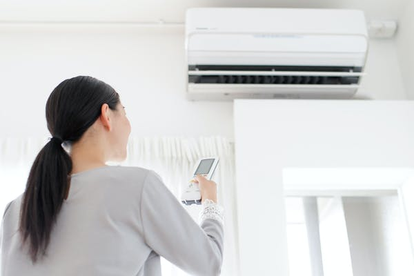 エアコンのリモコンを操作する女性