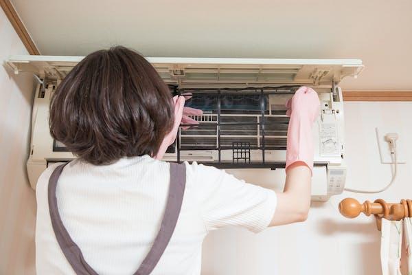 エアコンを掃除する女性
