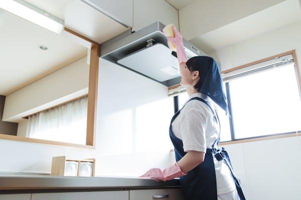 キッチンの換気扇を掃除するハウスクリーニングの女性