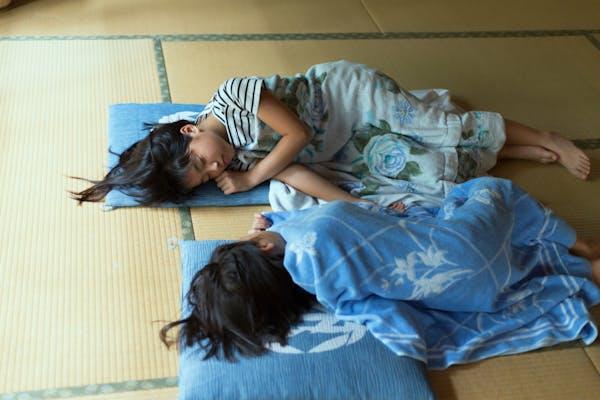 畳の上で眠る小学生の姉妹
