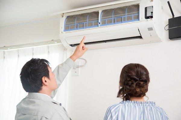 エアコンクリーニング業者と説明を受ける女性