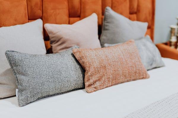 ベッド上に並べられた枕とクッション