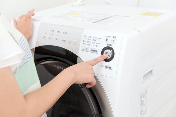塩素系クリーナーで洗濯槽を掃除する女性