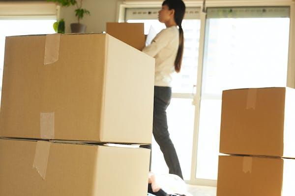 新居に引っ越して荷ほどきをする女性