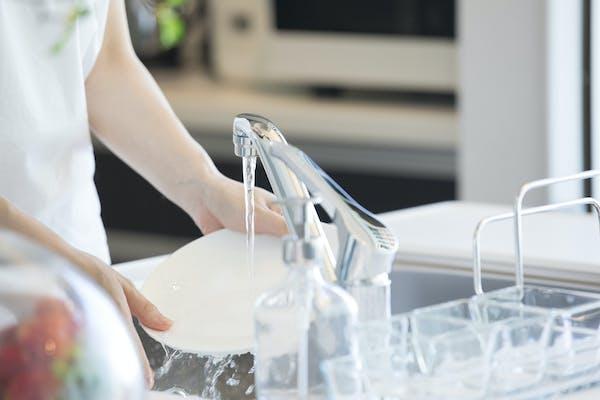 きれいなシンクで食器を洗う女性