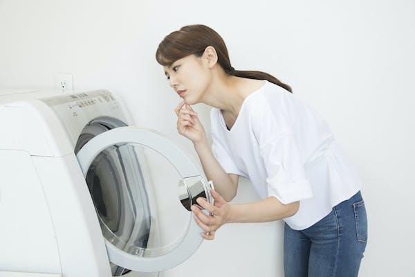 ドラム式洗濯機を眺める女性