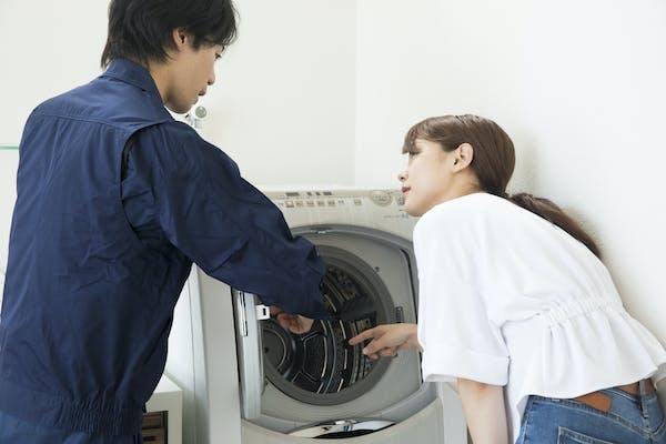 洗濯槽クリーニングをプロの業者に依頼している女性