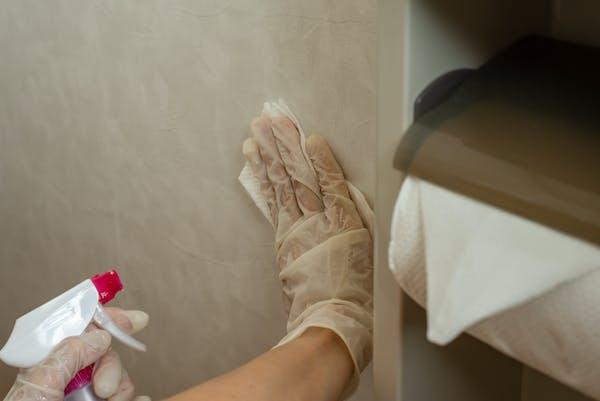 トイレの壁をスプレー洗剤と掃除シートで掃除