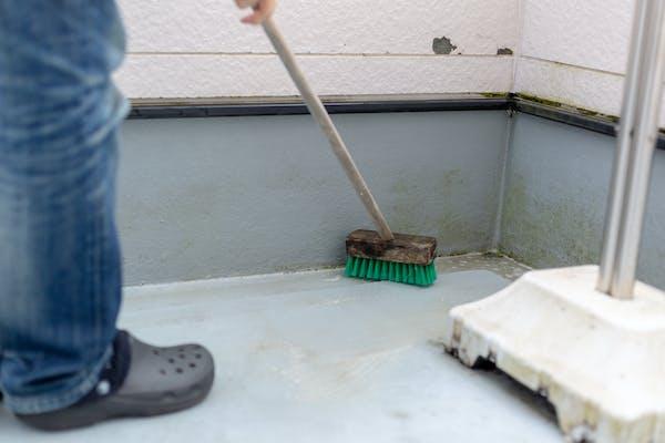 デッキブラシでベランダを掃除する様子