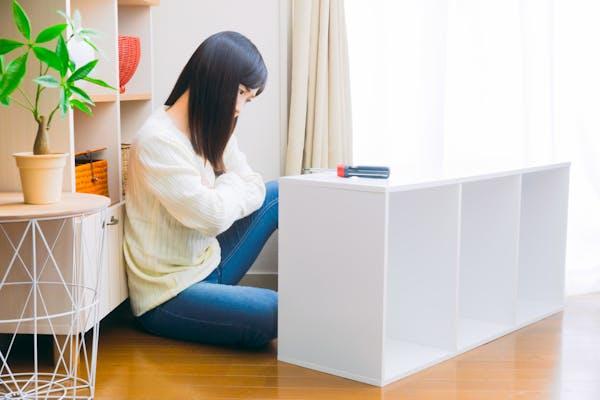 カラーボックスの使用方法を検討する女性