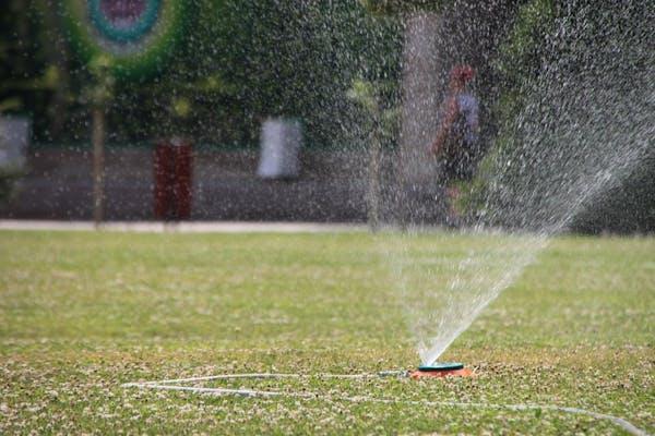 芝生にスプリンクラーで水を撒く