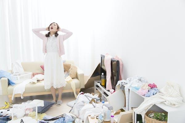 散らかった部屋に悩む女性