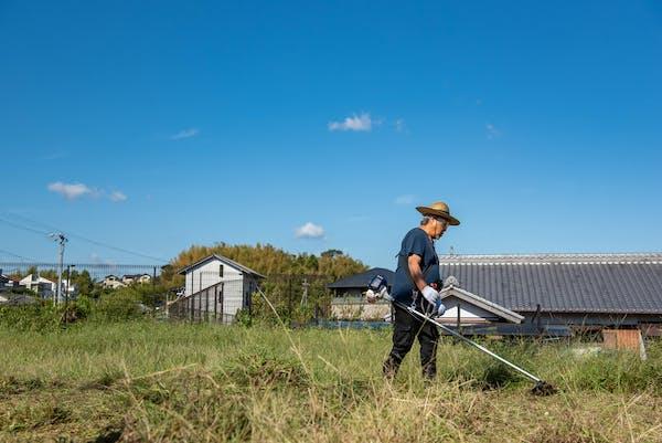 草刈りをする高齢男性