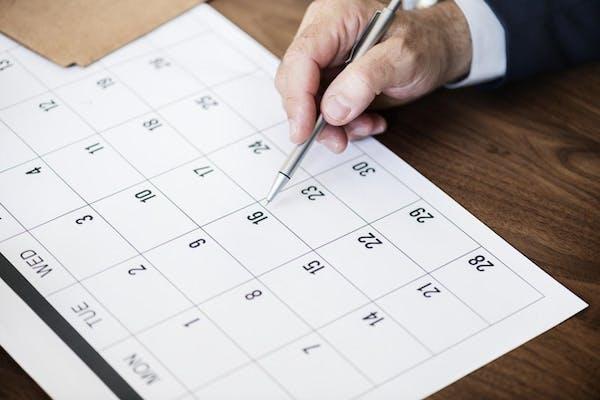 カレンダーをペンで示す男性の手元