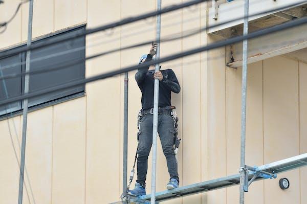 外壁塗装用の足場を組む若いとび職人