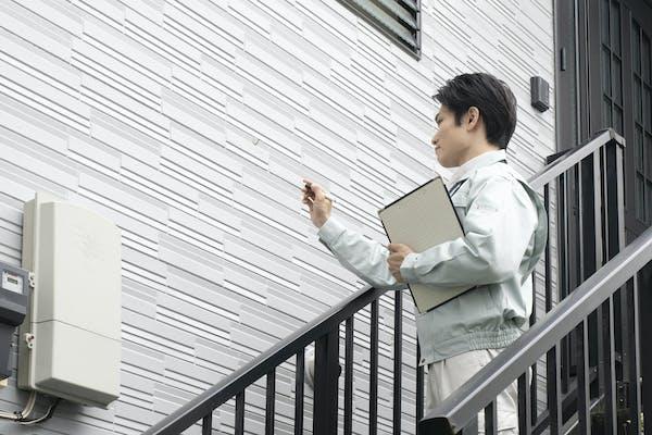 外壁塗装の見積もりをする営業マン