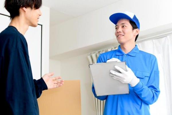 引っ越し業者と話す男性