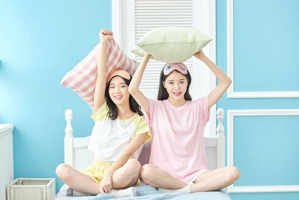 枕を持ち上げる2人の女性