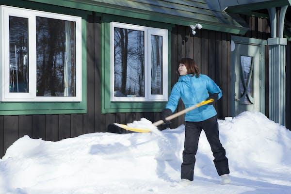 雪かきする女性