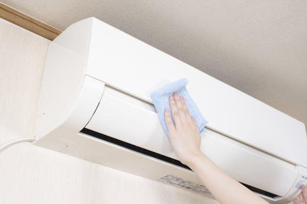 エアコンを青いタオルで拭く女性の手元