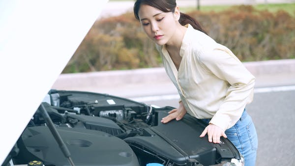 自動車のボンネットを開ける女性 故障